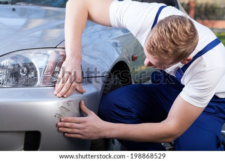 Mechanic in uniform assess the damage on the car - stock photo