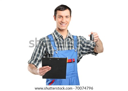 Mechanic in uniform holding a car key and clipboard isolated on white background - stock photo