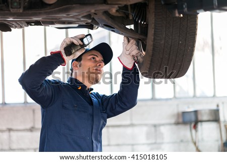 Mechanic inspecting a lifted car - stock photo