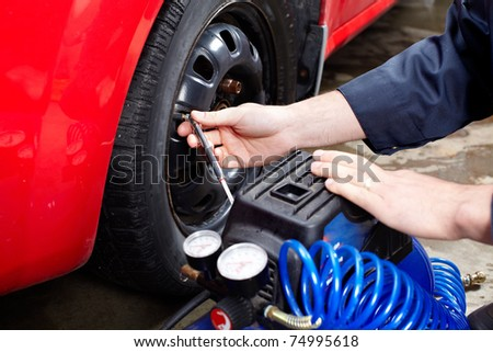 Mechanic inspecting the tire pressure in auto repair shop. - stock photo