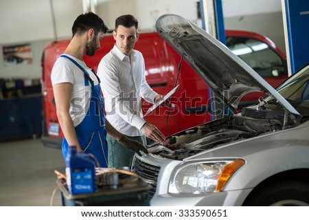 Mechanic inspection with manager on car damage - stock photo