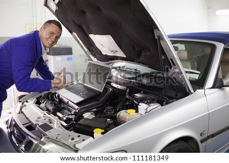 Mechanic leaning on a car engine in a garage