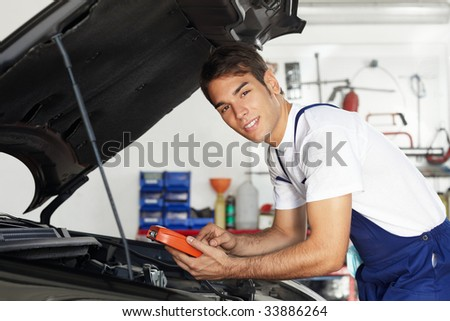mechanic leaning on bonnet with tester equipment and looking at camera
