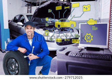 Mechanic leaning on tire while holding wheel wrenches against workshop - stock photo