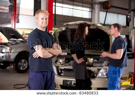 Mechanic looking at camera with customer and second mechanic in background - stock photo