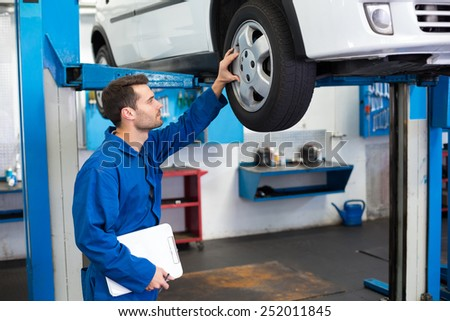 Mechanic looking at car tires at the repair garage