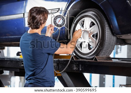 Mechanic Looking At Gauge While Inflating Car Tire - stock photo