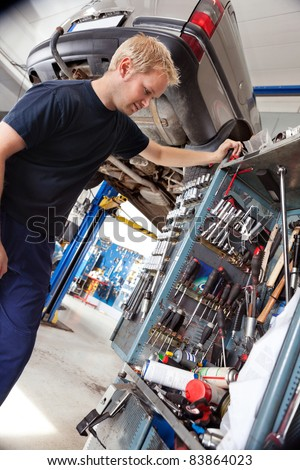 Mechanic looking at his tools and equipment in auto repair shop - stock photo