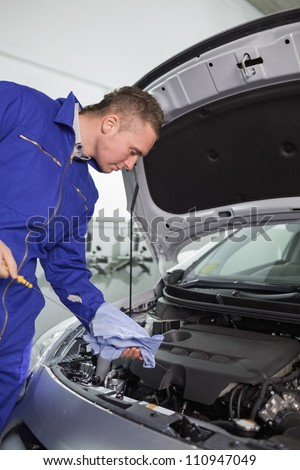 Mechanic looking at the dipstick in a garage