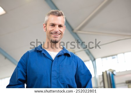 Mechanic looking down at camera at the repair garage - stock photo
