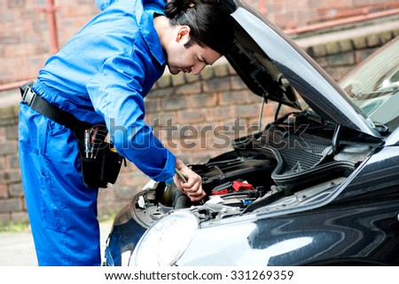 Mechanic looking into the car issue - stock photo