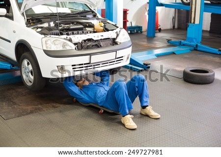 Mechanic lying and working under car at the repair garage - stock photo