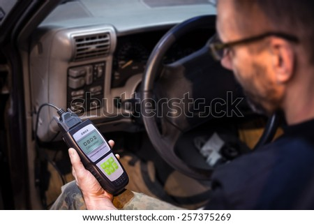 Mechanic making car diagnostics using obd device. OBD is On Board Diagnostics, an electronics self diagnostic system, typically used in automotive applications - stock photo