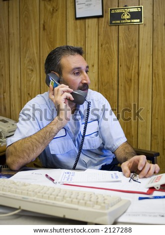 Mechanic on the phone conducting business with customer - stock photo