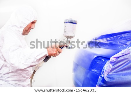 Mechanic painting a blue car in auto garage with airbrush