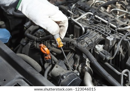 Mechanic performing the maintenance of a motor vehicle in - stock photo