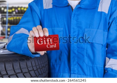 Mechanic person standing in the workshop while showing a gift card - stock photo