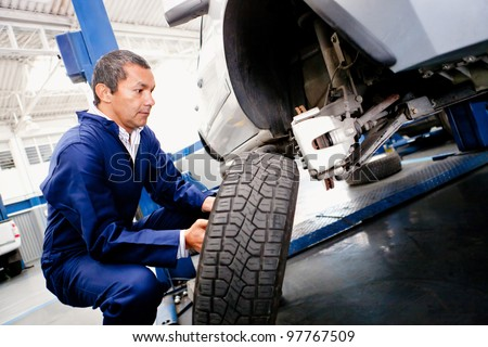 Mechanic placing a wheel back into a car - stock photo