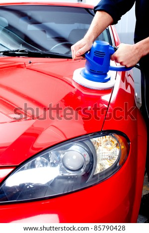 Mechanic polishing car in auto repair shop. - stock photo