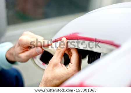 Mechanic preparing a car for painting by protecting the edges - stock photo