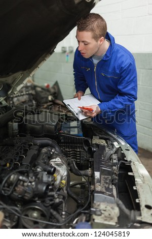Mechanic preparing checklist while looking at car engine - stock photo