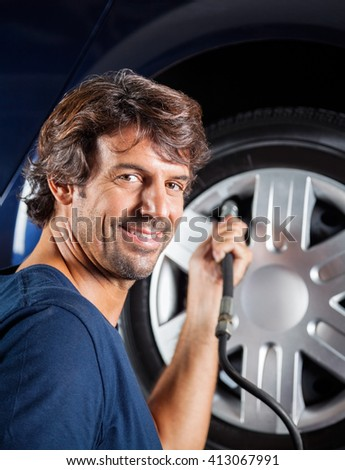 Mechanic Refilling Car Tire - stock photo