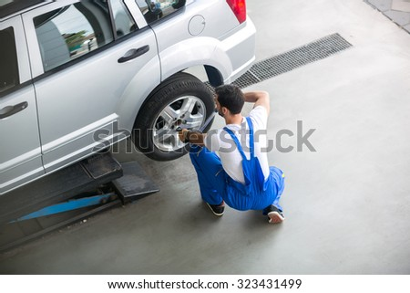 Mechanic removing a tire from a car with an air wrench - stock photo