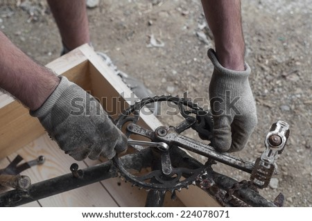 Mechanic repairing a bike, chainring and pedals - stock photo