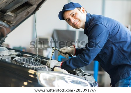 Mechanic repairing a car - stock photo