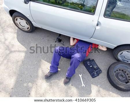 Mechanic repairing a car - stock photo