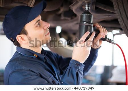 Mechanic repairing a lifted car - stock photo