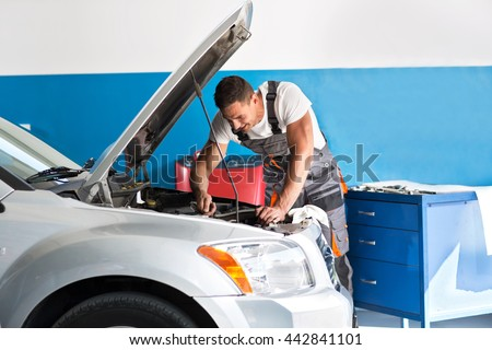 Mechanic repairing a lifted car at garage