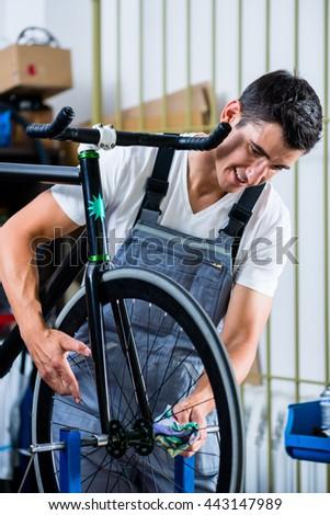 Mechanic repairing bicycle in his workshop - stock photo