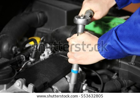 Mechanic repairing car with open hood