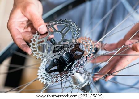 Mechanic repairing gears of bicycle - stock photo