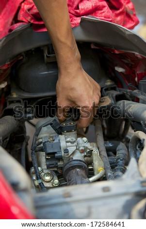 mechanic repairing motorbike holding adjustable wrench - stock photo