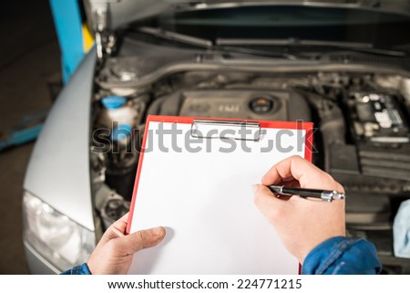 mechanic repairman inspecting car - stock photo