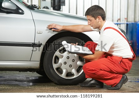 mechanic repairman inspecting car body during automobile car maintenance at auto repair shop service station - stock photo