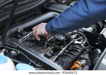 mechanic repairs a car in a garage - stock photo