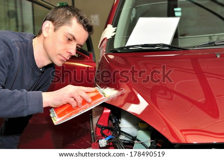 Mechanic repairs a red bonnet. - stock photo