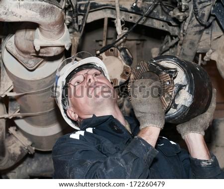mechanic repairs the car - stock photo