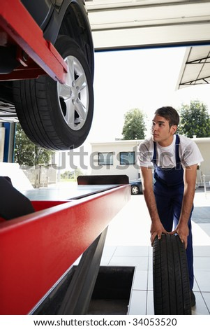 mechanic replacing car tyre in auto repair shop. Front view - stock photo