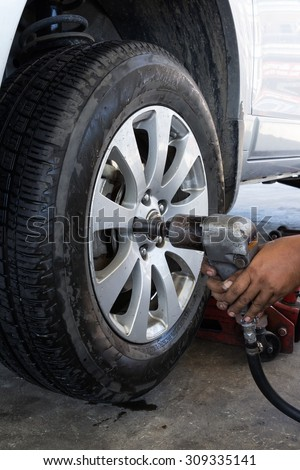 Mechanic screwing or unscrewing changing car wheel by pneumatic wrench  - stock photo