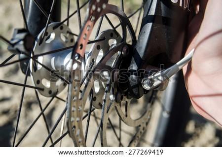 Mechanic serviceman installing adjusting bicycle gear on wheel - stock photo