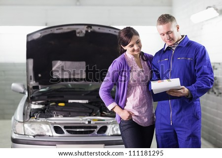 Mechanic showing a paper in a clipboard to a woman in a garage