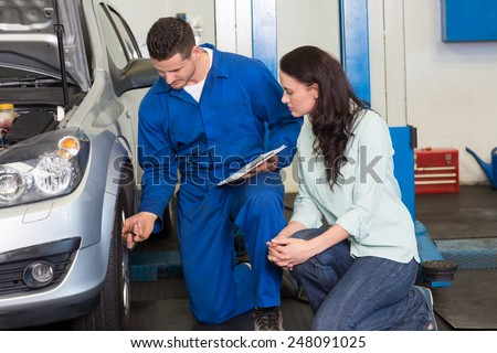 Mechanic showing customer the problem with car at the repair garage - stock photo