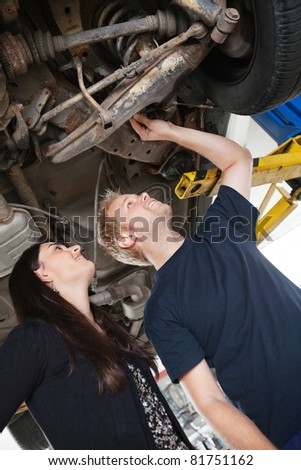 Mechanic showing female customer problems with car - stock photo
