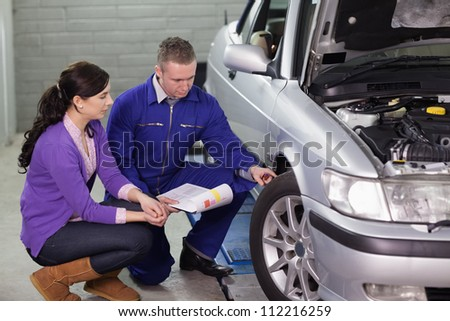 Mechanic showing the car wheel to a client in a garage - stock photo