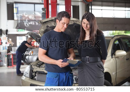 Mechanic showing the cost of service to female client while man working in background