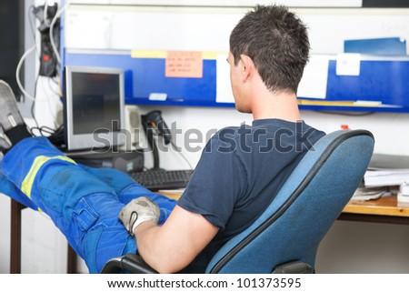 Mechanic sitting at desk in auto repair shop - stock photo